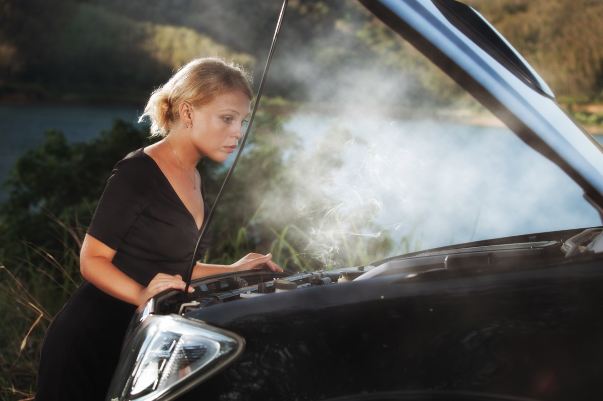 woman looking at engine with steam coming out